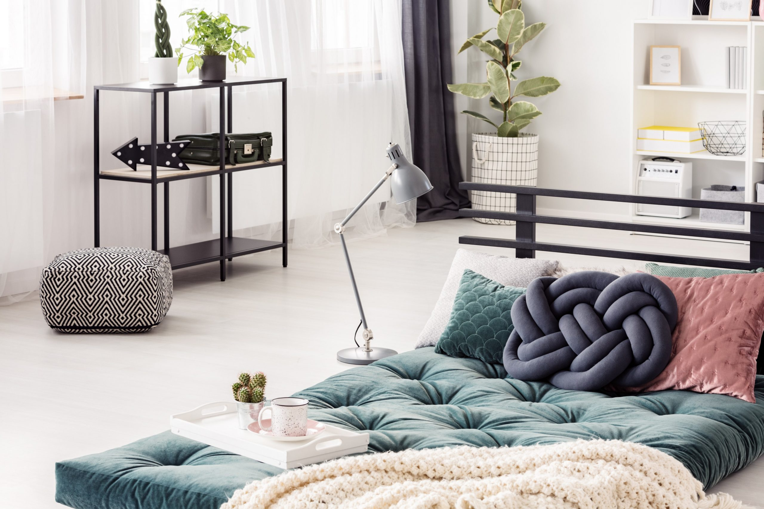 Blue-knot-pillow-on-green-futon-in-bright-bedroom-interior-with-patterned-pouf-and-lamp