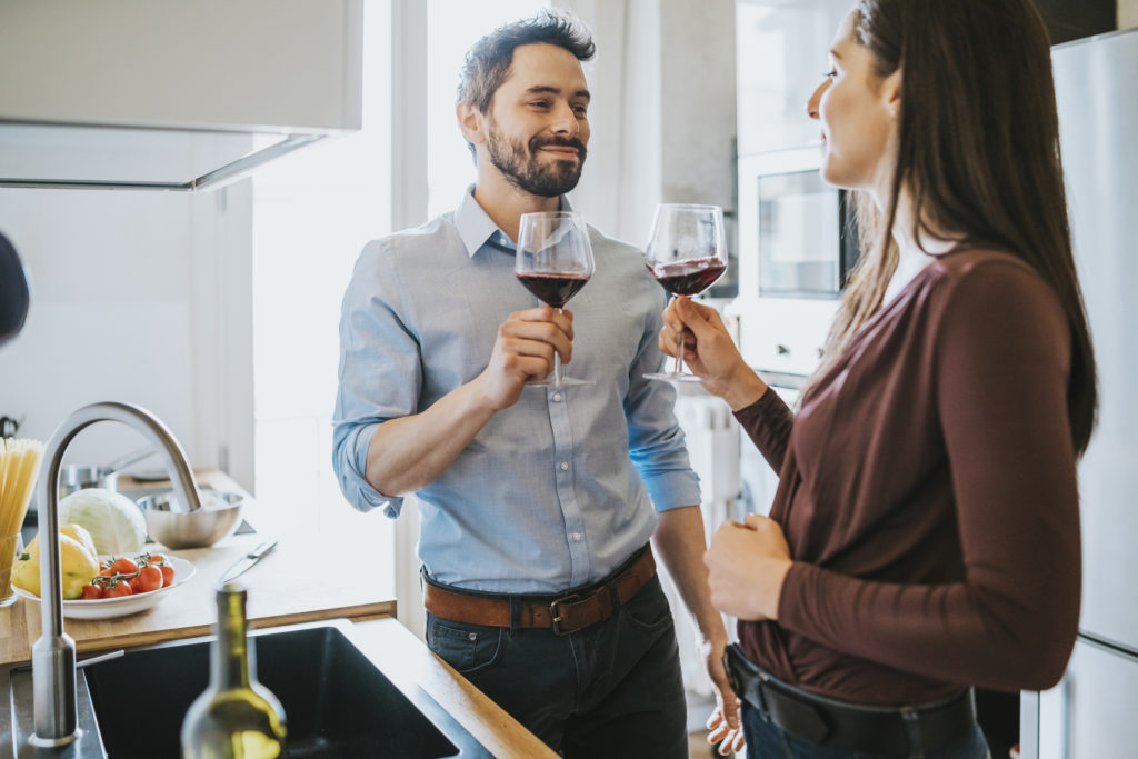 Loving couple celebrating in the kitchen toasting with red wine