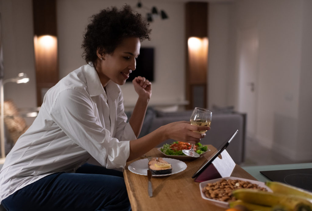 Happy mixed race woman proposing toast during online date