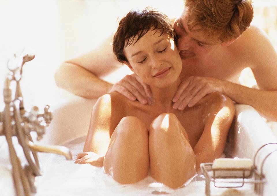 Woman taking bath, man massaging her shoulders