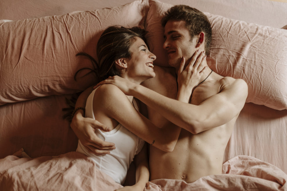 Happy young couple lying in bed