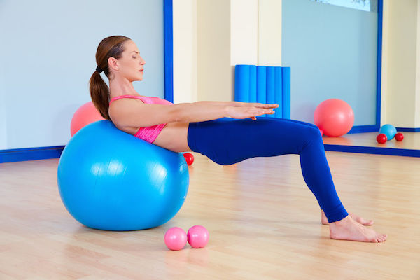 45054847 - pilates woman fitball swiss ball exercise workout at gym indoor