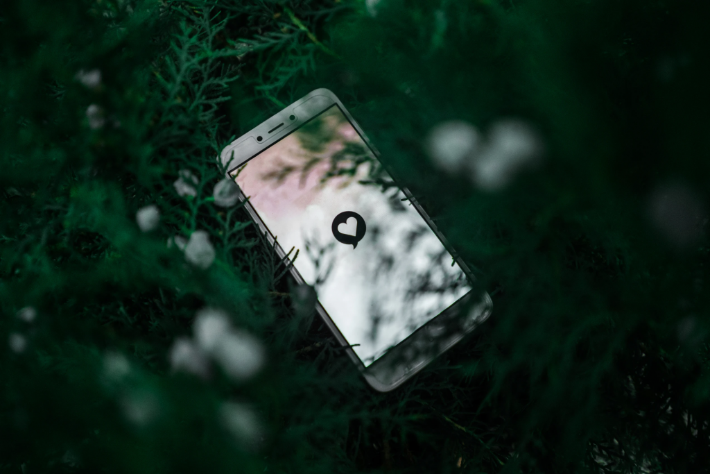 white smartphone near green plant